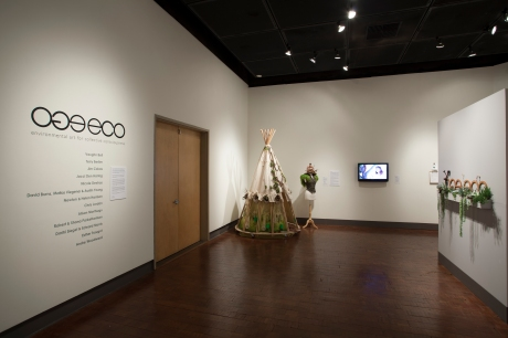 Gallery entrance view with title wall, Traveling SeedBomb dress and dress form with vest and hat and Urban Forgers video beside it. Photo: M.O.Quinn